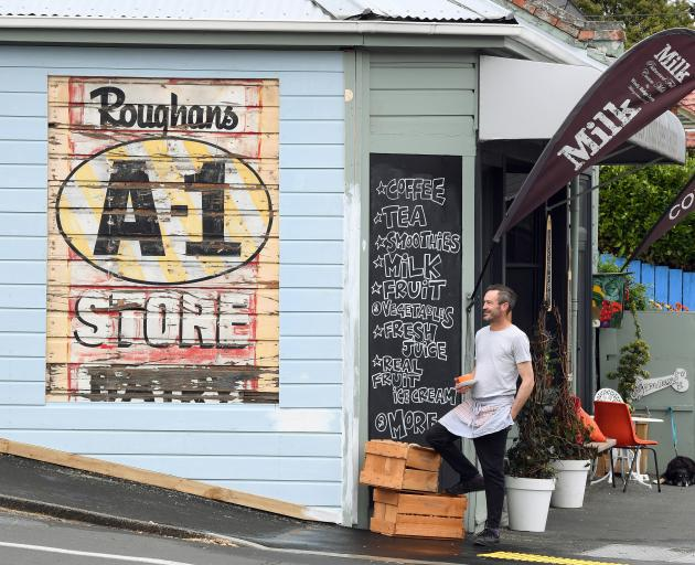 Blacks Road Green Grocer owner Christopher Wilson admires a recently uncovered sign on his 100-year-old shop. Photo: Stephen Jaquiery