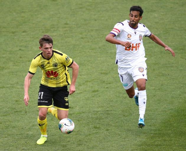 Callum McCowatt controls the ball for the Wellington Phoenix as the Perth Glory's Jaunde comes...