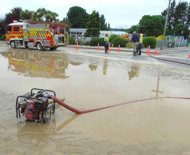 The Roxburgh Volunteer Fire Brigade helps to pump water off Roxburgh's main street after the November 2017 flood. PHOTO: SIMON HENDERSON