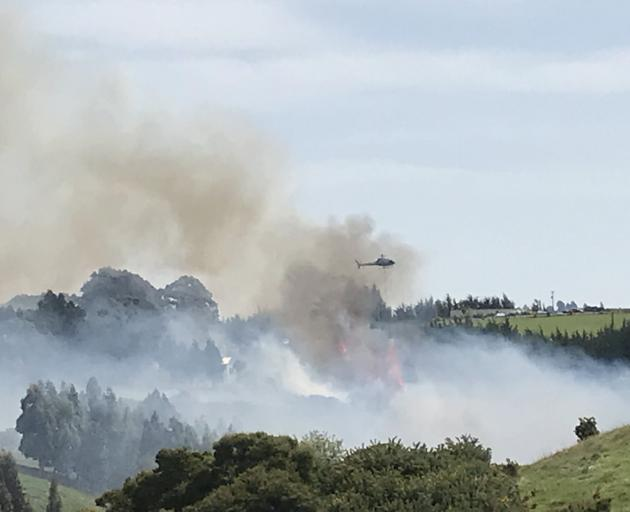 A helicopter with a monsoon bucket fights the fire on Scroggs Hill as seen from Kayforce St, Ocean View. Photo: Jacqueline Parsons