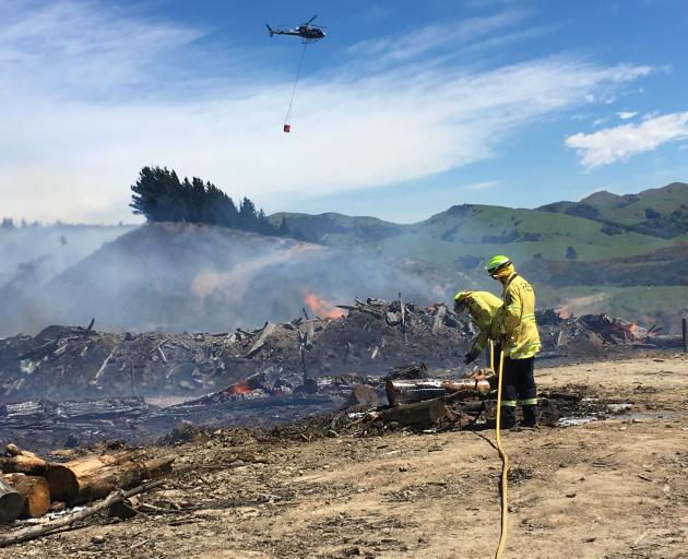 Firefighters battle the blaze at Bucklands Crossing while a helicopter with a monsoon bucket fights the blaze overhead. Photo: Stephen Jaquiery