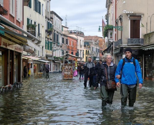 People walk in the flooded street during a period of seasonal high water in Venice. Photo: Reuters
