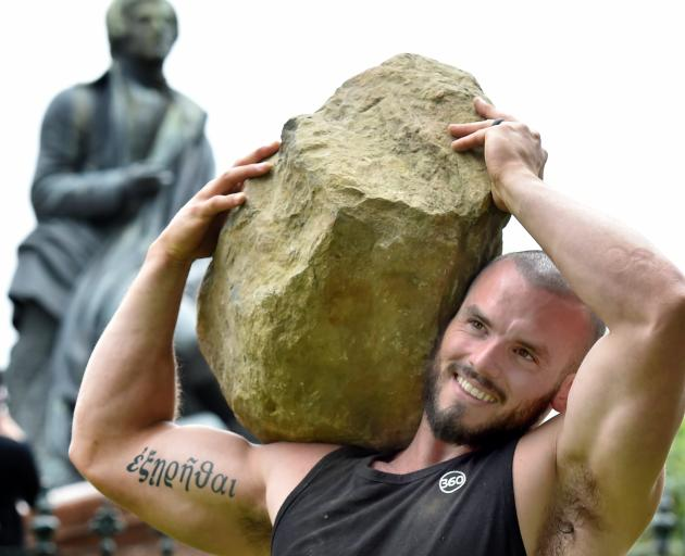 Police recruit Jayden Hill (31) proves his strength, lifting a 135kg rock in Dunedin's Octagon...