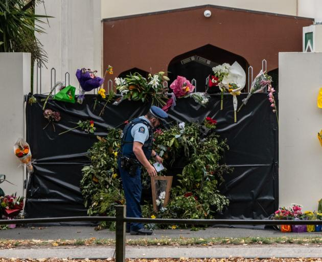 A policeman places flowers on the gates of the Al Noor mosque. Photo: Getty/ Carl Court