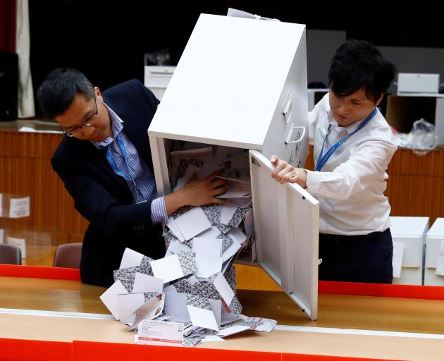 Officials open a ballot box at the polling station in the South Horizons West district as voting official closes in Hong Kong. Photo: Reuters