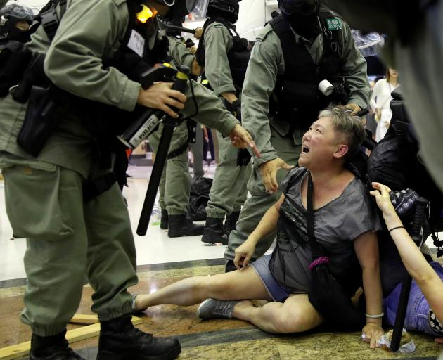 Riot police detain a woman during a protest at a shopping mall in Tai Po, Hong Kong. Photo: Reuters