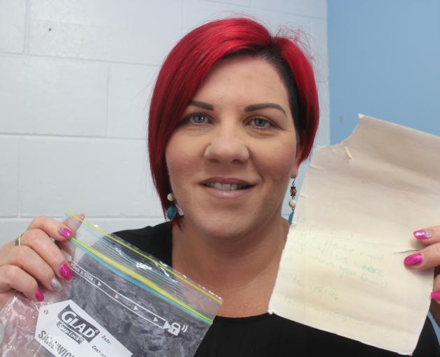 Greymouth's Leah Mead with the message her brother Ryan put in a plastic coke bottle 25 years ago...