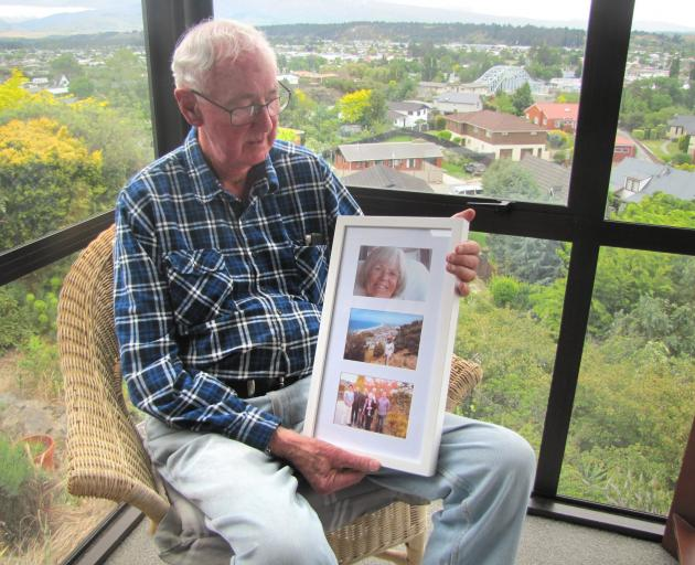 Ken Cook looks at photos of his wife Jeanette. Mrs Cook has advanced dementia and is in full-time...