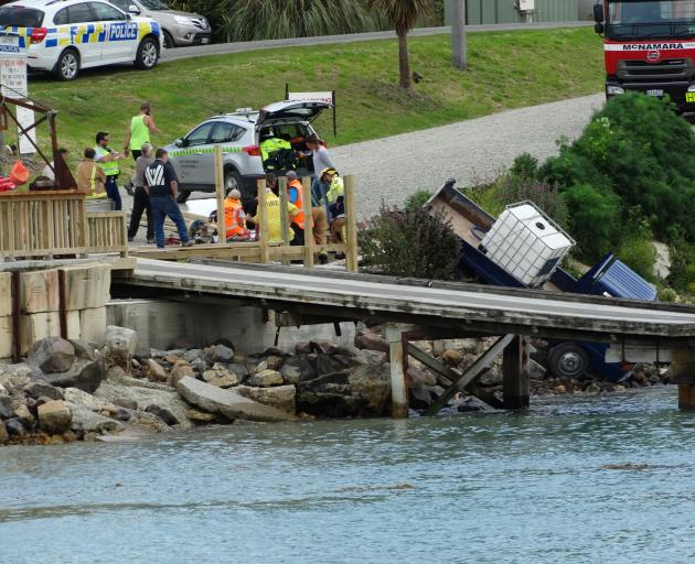 Emergency services tend to a man who was hit and injured by his own truck as it rolled towards the water in the seaside township of Moeraki yesterday. Photo: Daniel Birchfield