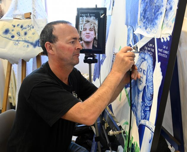 Ian Formston uses an air-brushing technique to paint a canvas with rock band theme. PHOTOS: LINDA...