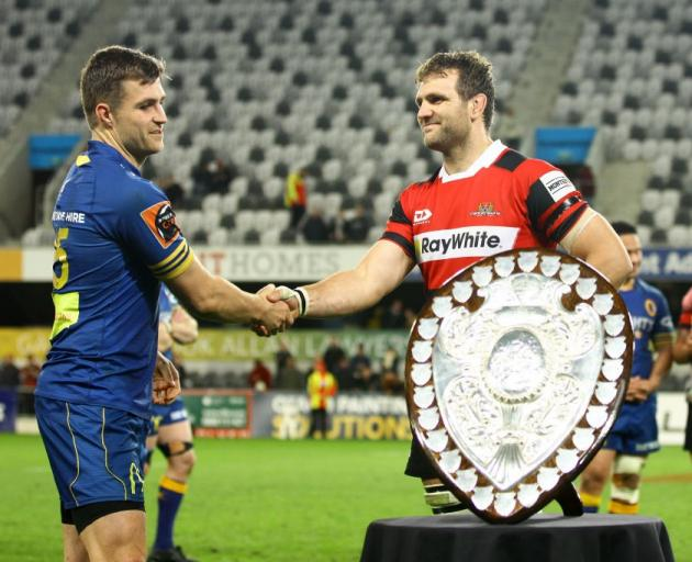 Captains Michael Collins (left) and Luke Whitelock shake hands as Otago hand the Ranfurly Shield...
