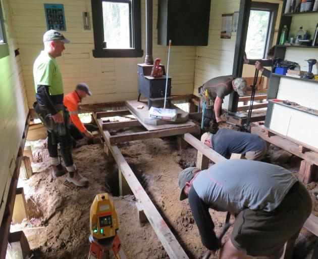 Members of the Wapiti Foundation remove flashings and lead-head nails during restoration work on...