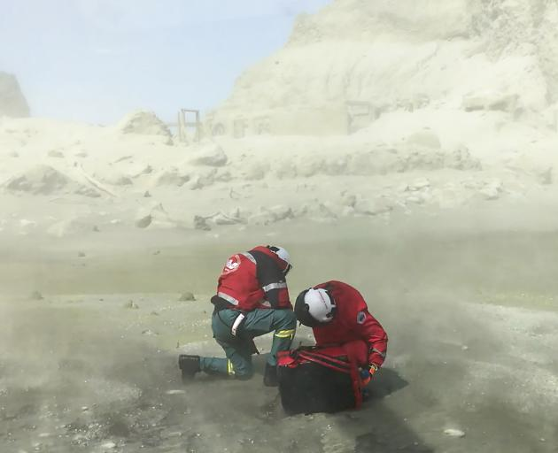The crew of the Westpac Rescue Helicopter shelters from the dust kicked up by their chopper during the initial rescue mission on White Island on Monday. Photo: Auckland Rescue Helicopter Trust