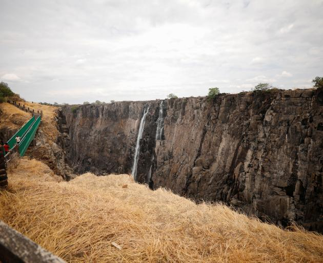 Visitors walk over a bridge as dry cliffs are seen along the parched gorge on the Zambian side of...