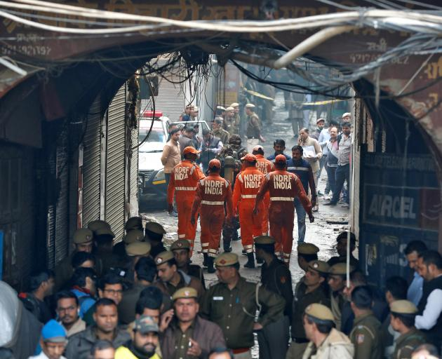 Members of NDRF head towards the site of a fire that swept through a factory where labourers were...