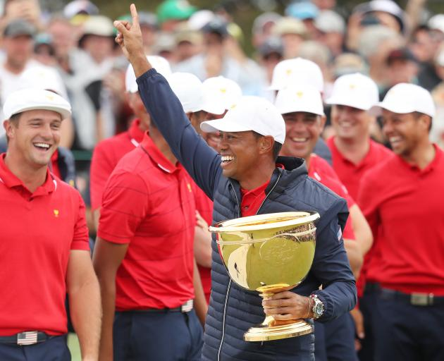 Tiger Woods celebrates winning the Presidents Cup in Melbourne yesterday. Photo: Getty Images