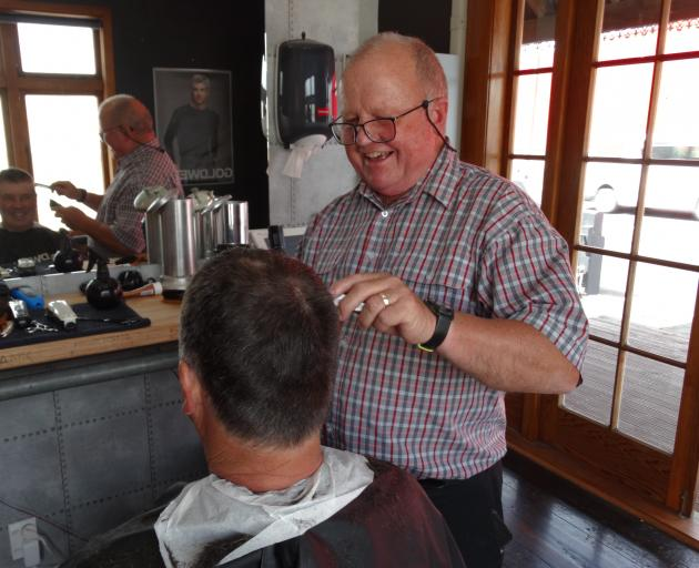 Oamaru hairdresser Ali Brosnan cuts Steve McLeod's hair yesterday on the 50th anniversary of the start of his career in the industry. Photo: Daniel Birchfield