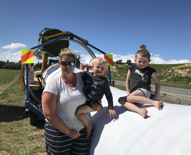 Fine weather has contractors out in force making winter feed. Sarah Byrne with children Liam (4) and Nikita (6) take a break from the truck carting bales to the wrapper. Photo: Alice Scott