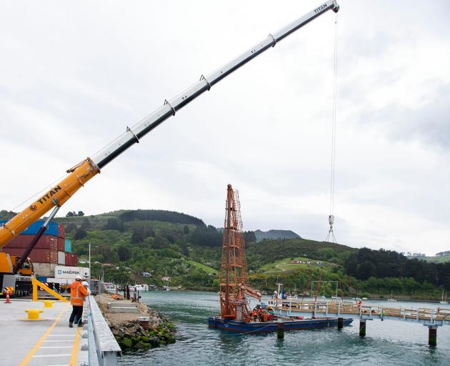 A giant crane manoeuvres sections of the Boiler Point fishing jetty into place during its...