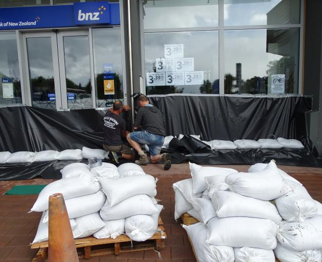 Jarvie Plumbers flood proofing the Wanaka BNZ branch yesterday afternoon ahead of a potential flood this morning. Photo: Kerrie Waterworth