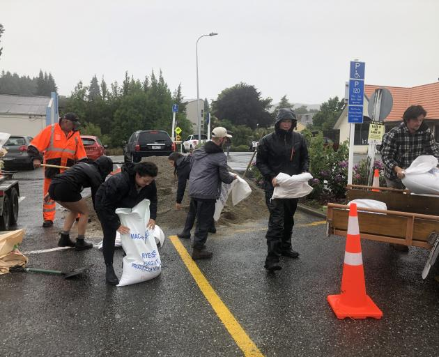 Volunteers arrive to fill sandbags soon after council staff and 6cum of sand arrived in the Dunmore St car park. Photo: Kerrie Waterworth