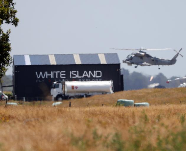 A military helicopter flies at the airport during the rescue mission following the White Island...