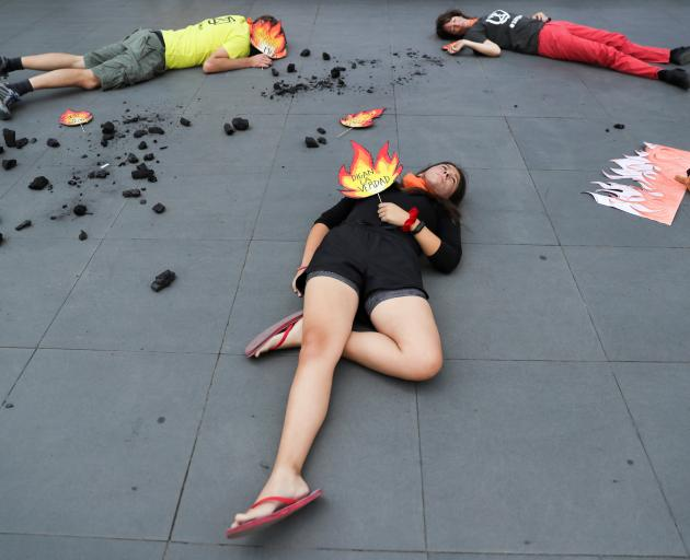 In Chile, protesters lay on the footpath during a demonstration outside the Australian embassy in...