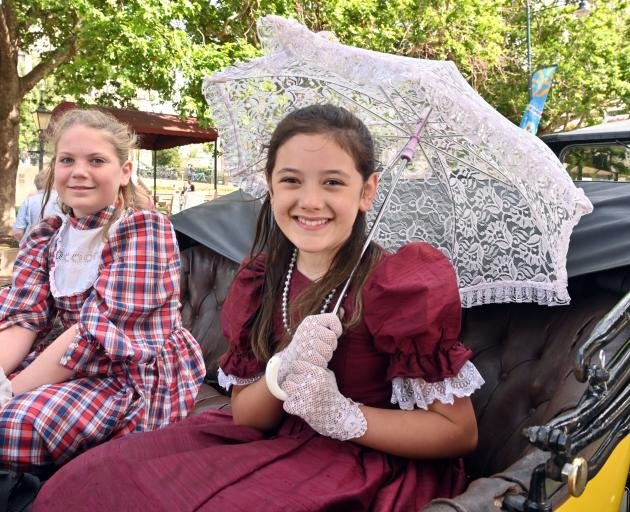 Jenifer Gough (11, left) and her friend Kiani Heperi (10), both of Mosgiel, ride in a 1914 Buick...