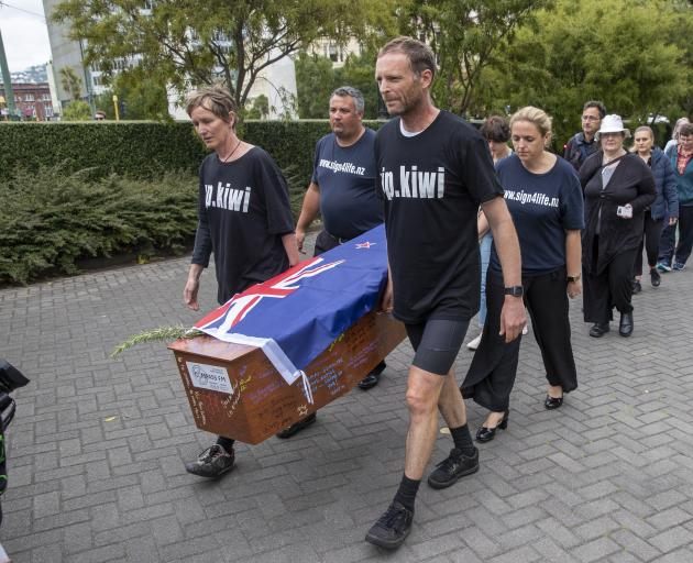 Camilla and Julian Cox and members of action group Patient Voice Aotearoa carry a coffin towards Parliament during their protest over Pharmac's budget. Photo: The New Zealand Herald