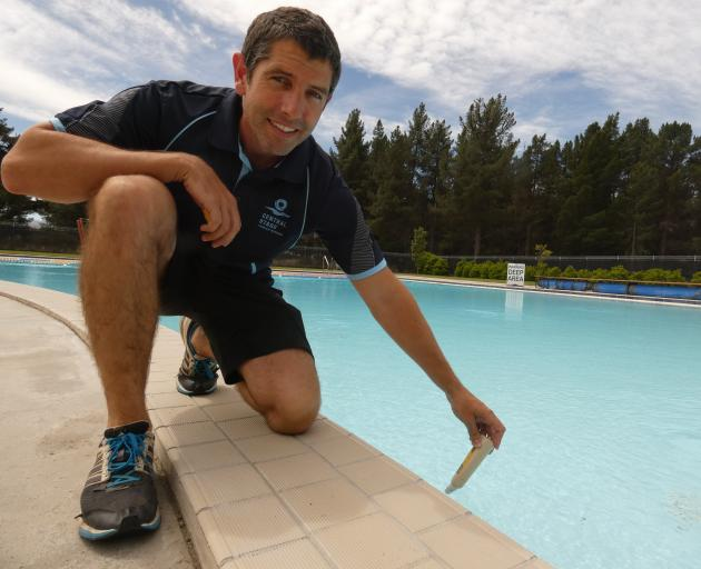 Molyneux Aquatic Centre team leader Nathan Chapman checks the temperature of Alexandra's outdoor pool after cool weather prevented it from opening as regularly it has in as other seasons. Photo: Alexia Johnston