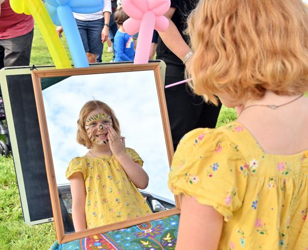 Checking out her newly painted cat face is Grace Tagg (6), of Brighton.