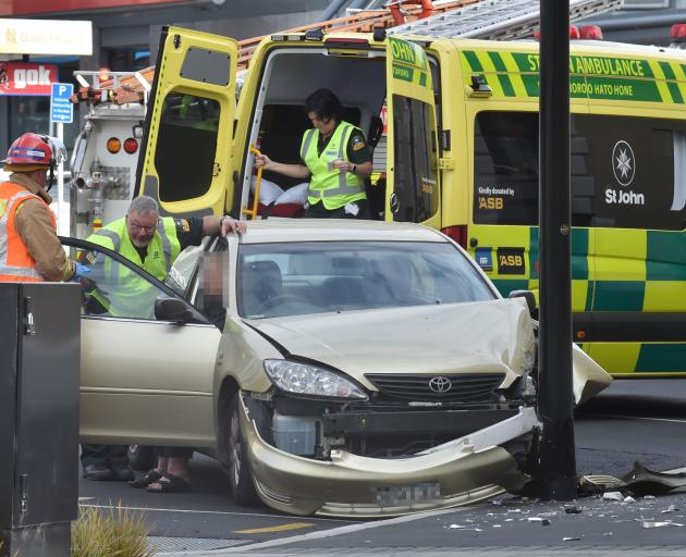 A St John Ambulance officer checks on the driver of a car involved in a crash in Moray Pl near...