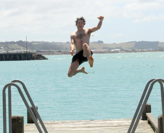 Celebrating his 26th birthday, Henry Elsom, of Oamaru, jumps off a jetty at Oamaru Harbour yesterday. Photo: Hamish MacLean