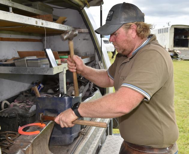 Farrier Jordan Dent, of Fairlie, prepares to replace a shoe for a horse competing in yesterday's...