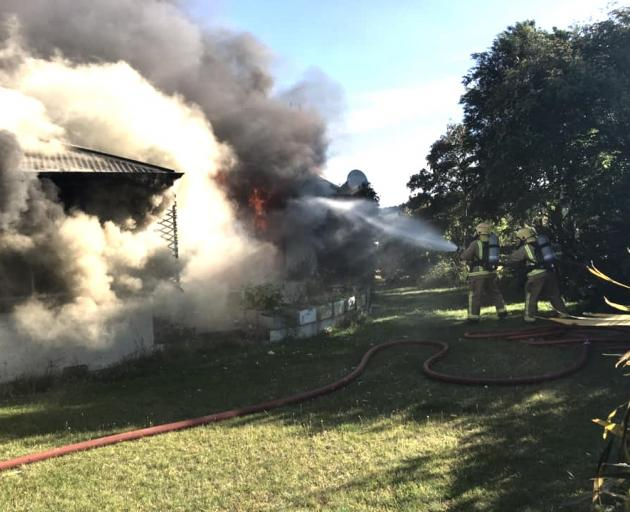 Volunteer firefighters tackle a house fire near Te Anau yesterday. Photo: Te Anau Volunteer Fire...