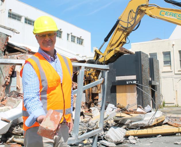 HWCP director Scott O'Donnell holds a brick from a massive demolition task that signals the start...