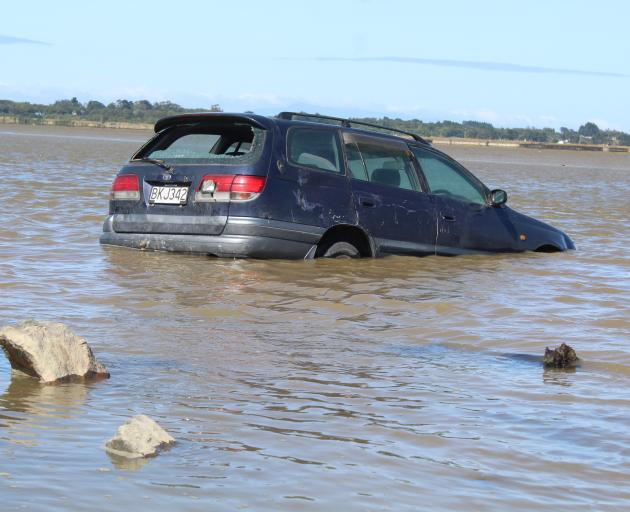 A car with a smashed rear window was found half submerged in an Invercargill estuary yesterday....