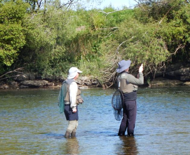 Chris Cowie on the SFFC course plays a trout on the Mataura while instructor Chris McDonald...