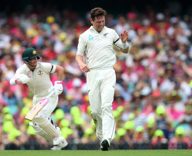 Matt Henry of New Zealand reacts while fielding off his own bowling during day one of the test...
