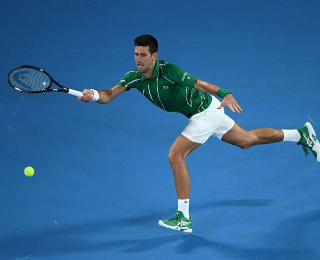 Novak Djokovic reaches for a shot during his first round match at the Australian Open. Photo:...