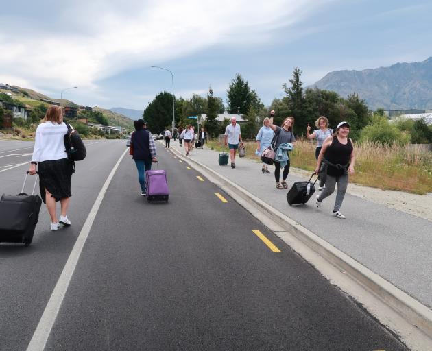 Travellers head towards and away from Queenstown Airport on Saturday morning on foot after a...