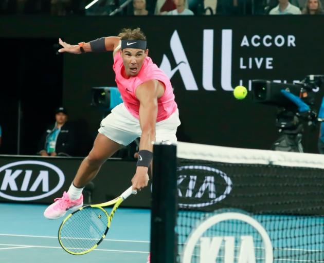 Rafael Nadal reaches for a backhand during his Australian Open win over Nick Kyrgios. Photo:...
