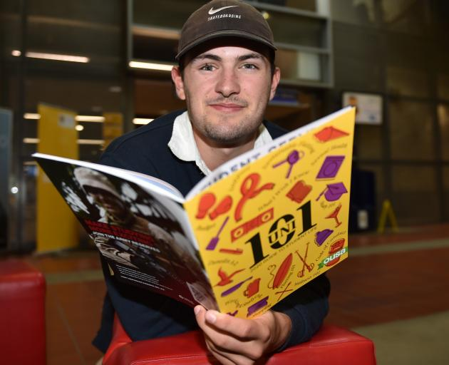 University of Otago information science student Liam Todd looks at a student handbook on the...