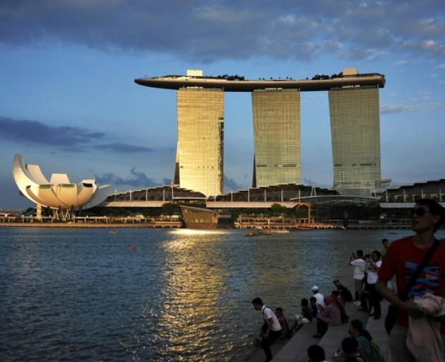 People sit on the waterfront as sunlight shines on the Marina Bay Sands resort in Singapore....