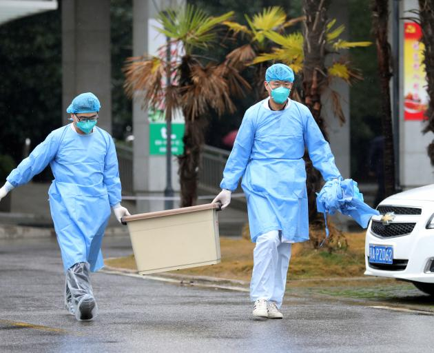 Medical staff carry a box as they walk at the Jinyintan hospital, where the patients with pneumonia caused by the new strain of coronavirus are being treated, in Wuhan. Photo: Reuters