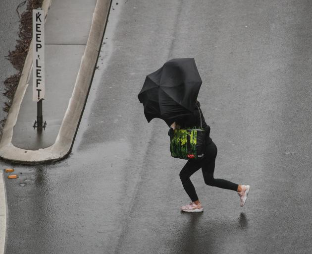 A pedestrian braves strong wind and rain in Sydney at the weekend. Photo: Reuters