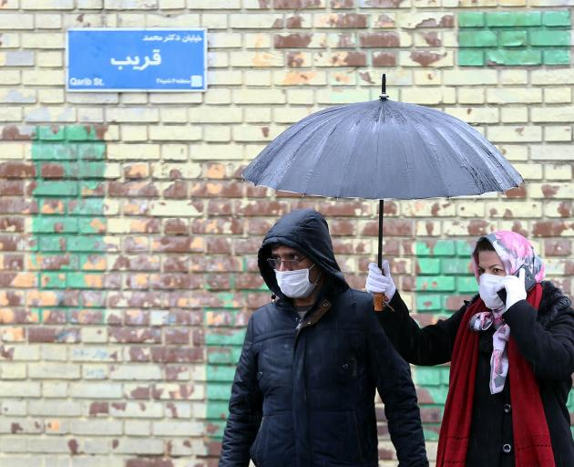 Iranian people wear protective masks as they walk in the street in Tehran. Photo: WANA (West Asia...
