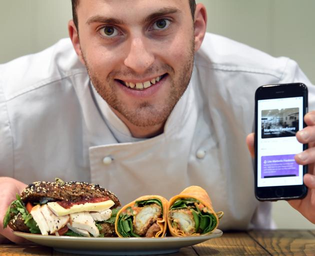 Marbecks Foodstore chef Jean-Baptiste Rousselot with the foodstore's page on a mobile app, intended to cut food waste. Photo: Peter McIntosh