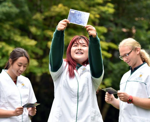 University of Otago pharmacy student Angela Fan (19, centre) holds up a message card, while...