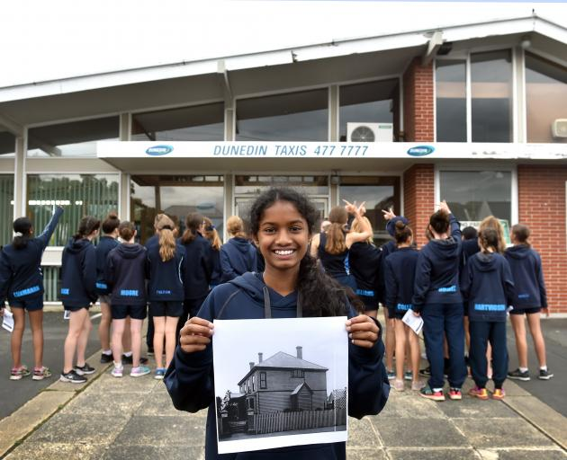 St Hilda's Collegiate School year 9 pupil Thareni Luxmanan (13) holds a photo of how the school looked at its first site on Leith St, while fellow pupils examine the building on the site now. Photo: Peter McIntosh